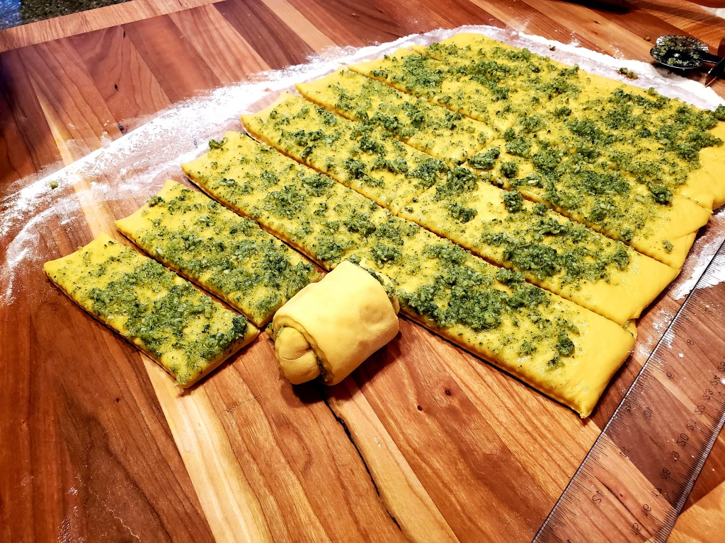 rolled out dough with pesto on top cut into strips.