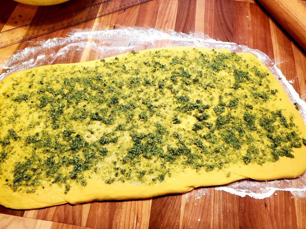 rolled out dough with pesto on top