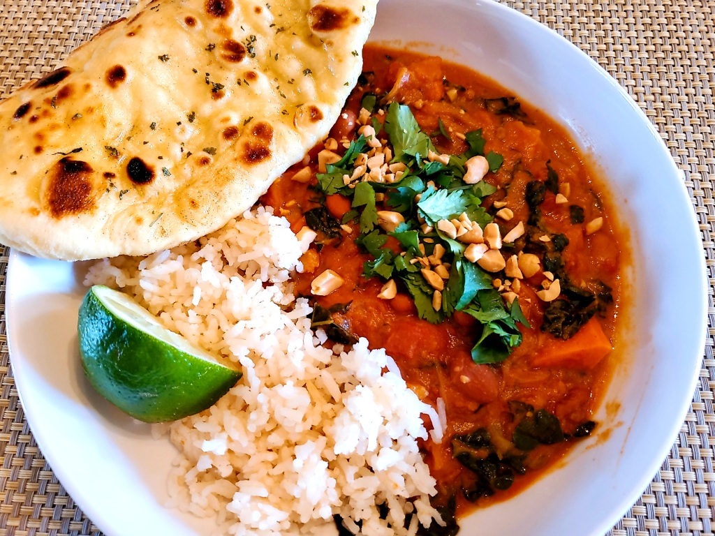 Plated African Peanut stew with rice and Naan bread